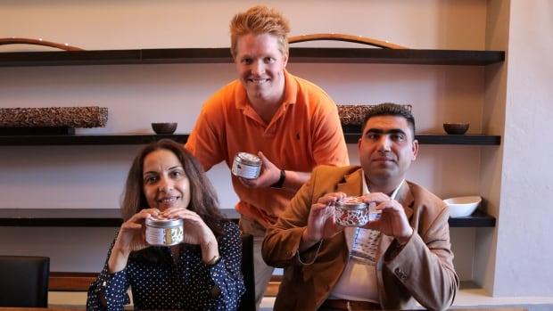Interpreter Bushra Alarim, SuraiTea founder Kevin Smiley and Syrian refugee Abduallah Alnassan hold tins of jasmine tea.
