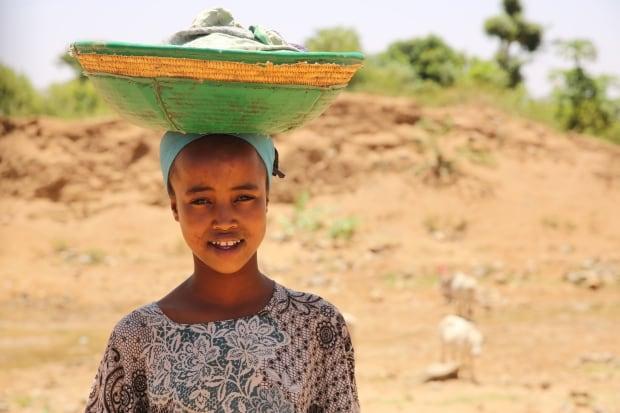 Ethiopian girl carrying goods in basket
