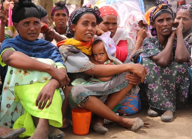 Mothers wait with babies at food distribution centre