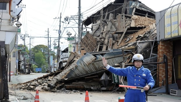 A police officer stands guard in front of a house destroyed by an earthquake in Mashiki, Kumamoto prefecture, southern Japan on Saturday. Wednesday's tremor is the latest in a series of strong quakes to hit the region.