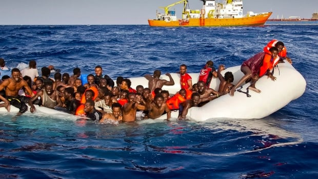 Refugees ask for help from a dinghy boat as they are approached by the SOS Mediterranee's ship Aquarius on Sunday. The UNHCR said up to 500 people are feared dead in the sinking.
