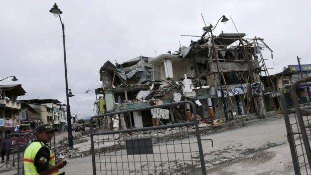 A police officer stands guard next to a collapsed building in Pedernales, Ecuador, a week after a massive earthquake struck off the country's Pacific coast.