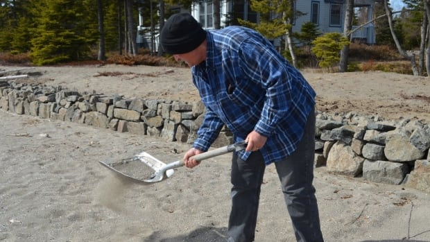 Chuck Hutterli modified a shovel by fitting it with a mesh net to sift through the sand, so that he can collect the plastic pellets from the beach in front of his home near Nipigon, Ont.