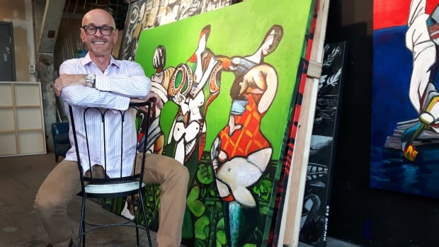 Artist Tiko Kerr sits with some of the works that will appear in his Body Language exhibit.