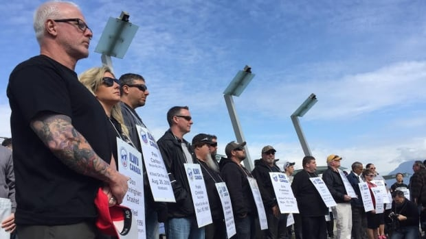 People gathered at Jack Poole Plaza in Vancouver for a 2016 ceremony for the National Day of Mourning. Each person pictured is wearing a placard bearing the name of a worker who died in a work accident or from an occupational disease.