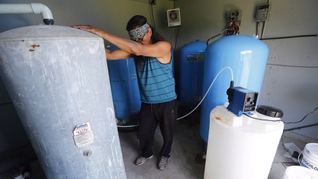Kavin Redsky, a water plant operator at Shoal Lake 40 First Nation in northwestern Ontario, prepares to treat water from the lake with chlorine in 2015. The community is scheduled to get a new water treatment plant in 2021 following the construction of a road linking the community to the Trans-Canada Highway.