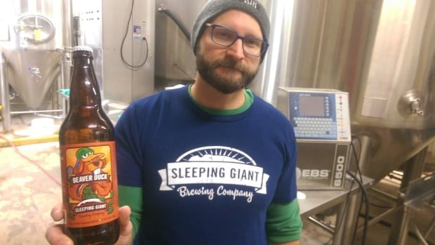 Kyle Mulligan, Sleeping Giant Brewing Company's head brewer and co-owner, holds a bottle of the brewery's award-winning Beaver Duck APA.