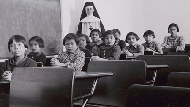 A group of female students and a nun pose in a classroom at Cross Lake Indian Residential School in Cross Lake, Manitoba in a February 1940 archive photo.