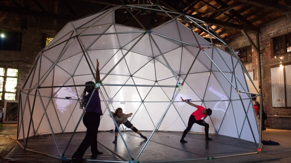 Dancers from the T Lang Dance Company perform in a geodesic dome. The LuminAI dances with them, learning and collaborating instead of just mimicking.