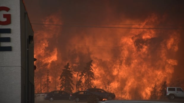 Flames are seen from the Sawridge Motel in Fort McMurray, Alta., on Tuesday. The entire city of 60,000 has been ordered evacuated.