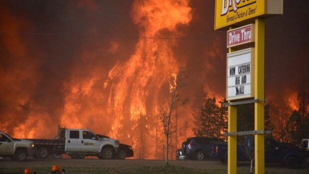 A wall of fire rages outside of Fort McMurray, Alta. Tuesday May 3, 2016. Raging forest fires whipped up by shifting winds sliced through the middle of the remote oilsands hub city of Fort McMurray Tuesday, sending tens of thousands fleeing in both directions and prompting the evacuation of the entire city.