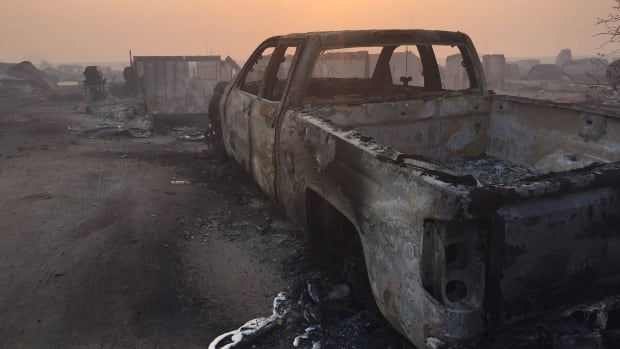 A burnt-out truck in the Beacon Hill area of Fort McMurray, Alta., where a wildfire that started in May has led to billions in insurable damages.