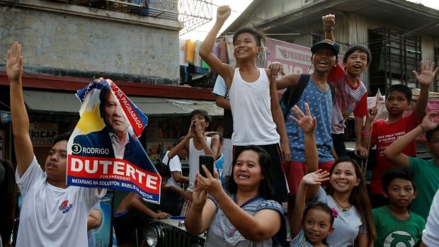 "Supporters watch the motorcade of presidential candidate Rodrigo ""Digong"" Duterte (not pictured) during election campaigning in Malabon, Metro Manila in the Philippines."