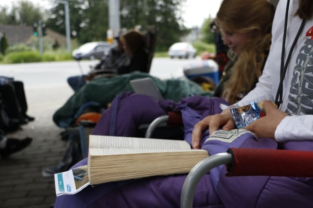 Reading books while waiting in line for condos in Langley