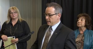 Yukon Health Minister Mike Nixon, flanked by Health Assistant Deputy minister Sherri Wright, left, a