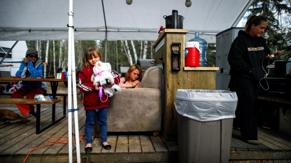 Evacuees from the Fort McMurray wildfires, Ellyse Naughton (L), holds her toy robotic dog as her mother Erin looks at her phone as they camp at the Christina Lake campground in Conklin, Alberta, Canada, May 5, 2016. (Mark Blinch/Reuters)
