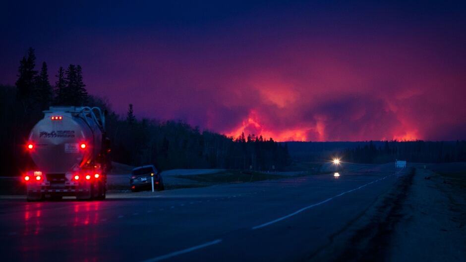 A truck drives on a highway as wildfire burns south of Fort McMurray, Alberta, Canada, on Wednesday, May 4, 2016.