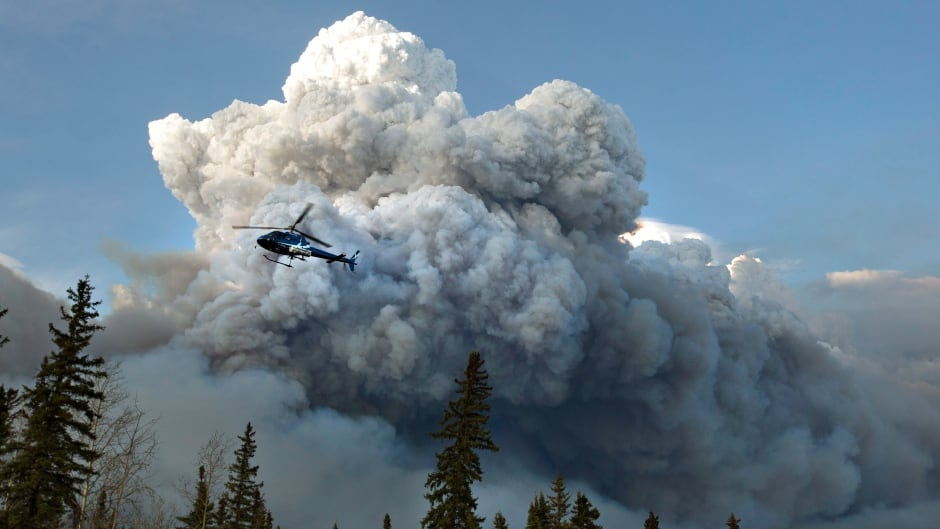 A helicopter flies past a wildfire in Fort McMurray, Alta., on Wednesday May 4, 2016.