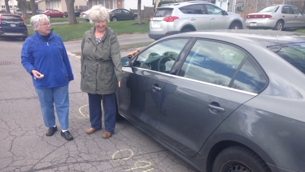 Diane Day, left, and Danielle Sullivan, right, stand next to a car they've marked with chalk. The two women patrol the streets around Ottawa's CSIS and CSE headquarters, keeping an eye out for drivers who've overstayed their welcome.