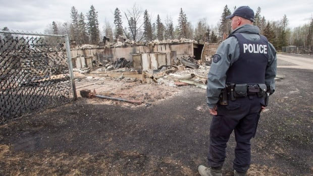 A police officer looks at the wildfire destruction in the Abasands neighbourhood of Fort McMurray. Property owners could be facing a hike in insurance premiums.