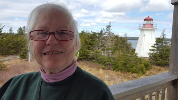 Florence Nygaard with the community's 125-year-old lighthouse in the background.