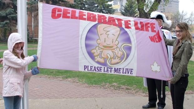 Sisters Melena and Tatiana Kawula hold up the Celebrate Life Week flag at Prince Albert City Hall in May 2016.