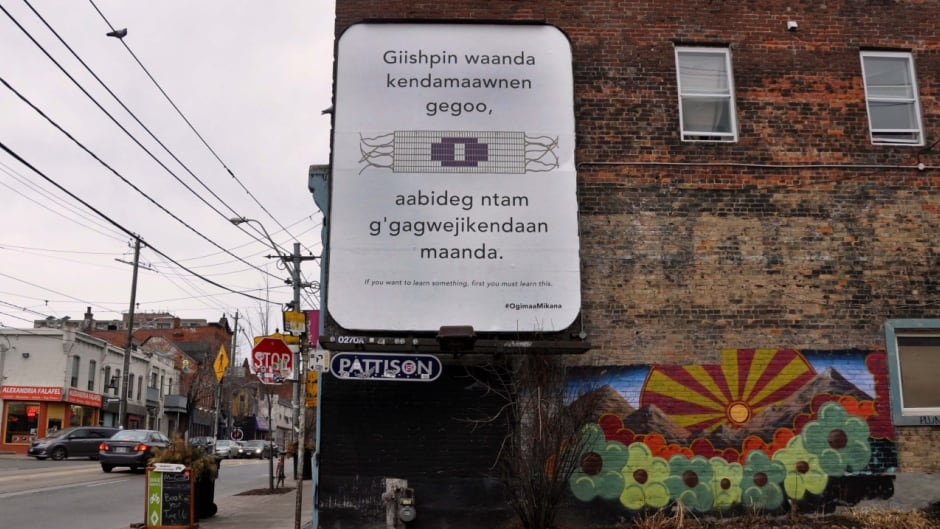 """This billboard on the corner of of Queen Street West and Noble Street in Toronto's Parkdale neighbourhood is in Anishinaabemowin, the Ojibway language.  In English it translates to """"If you want to learn something, first you must learn this."""""""
