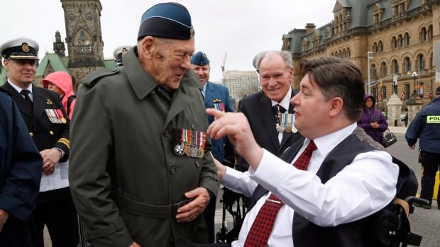 Minister of Veterans Affairs Kent Hehr talks with veterans during the Battle of the Atlantic memorial services on Parliament Hill. Government lawyers are taking veterans back to court over lifelong pensions for disabled and injured veterans.