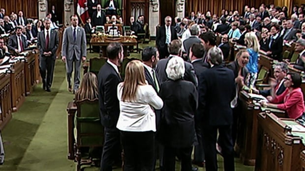 In a still image from House of Commons video, Prime Minister Justin Trudeau, centre-right, is seen reaching in for Conservative whip Gord Brown, centre, as NDP Leader Tom Mulcair, centre-left, stands by. The video shows the prime minister bumping NDP MP Ruth Ellen Brosseau, right.