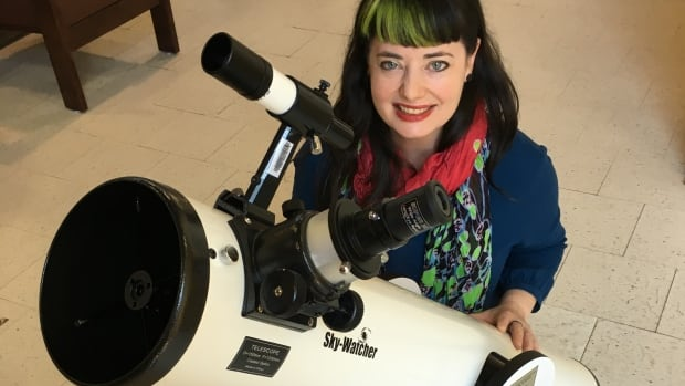 Assistant librarian Gillian Mahen displays the Dobsonian reflecting telescope at the Confederation Public Library.
