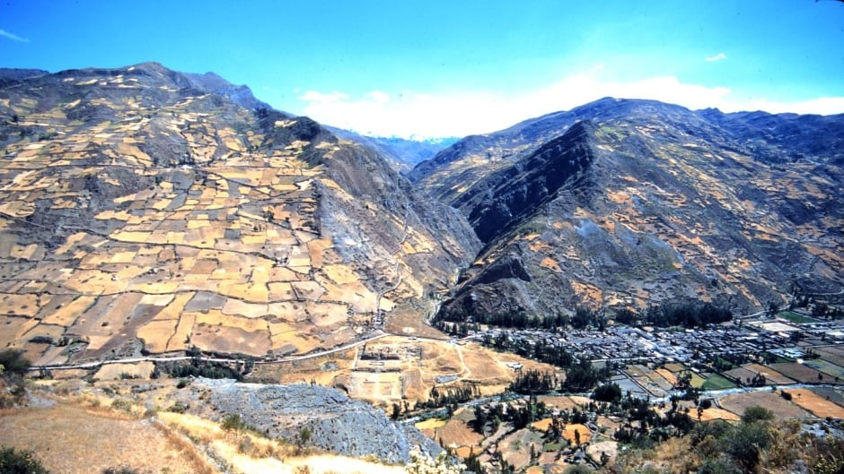 Chavín de Huántar, Peru, with site in middle, modern town on the right and the Cordillera Blanca mountains visible in the distant centre.