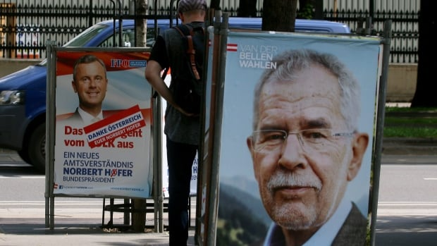 A man walks between election posters of Alexander Van der Bellen, former head of the Austrian Greens, right, and Norbert Hofer of Austria's right-wing Freedom Party, FPOE, left, in Vienna on Monday. Van der Bellen won the presidential election by a narrow margin.
