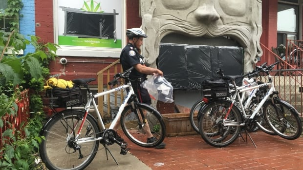 A Toronto police officer bags evidence outside a marijuana dispensary in Kensington Market. Police executed search warrants at a number of dispensaries where they allege trafficking has occurred.