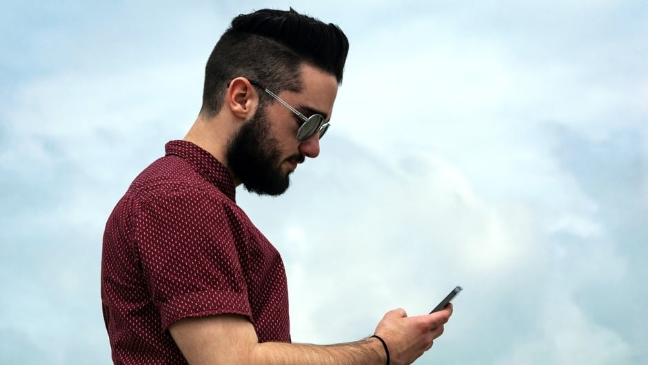 A millennial looks intently at his smartphone.