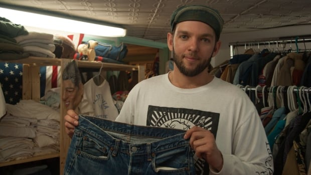 Vintage seller Kirby Fisher holds up a pair of rare denim jeans in his showroom.