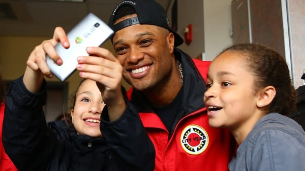 Gia Culbertson, 9, left, and Lynneah Childs, 10, take a selfie with Seattle Mariner Robinson Cano this week. Children use phones more for photos and text-messaging than for making calls.