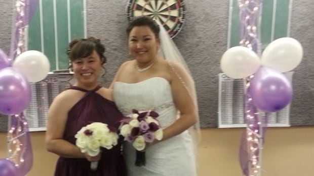 Liz Gordon and Shannon Clarke pose for a photo at Clarke's wedding in 2014. The sisters were separated when Clarke was given up for adoption, but 14 years later they discovered they'd been walking the halls of the same school for years.