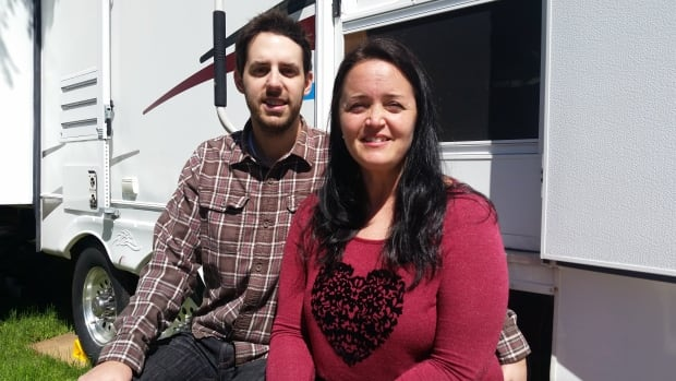 """Adam Doolittle and Kate McCallum in front of their home, an RV they plan to pull across the country as part of a """"workamping"""" experience."""