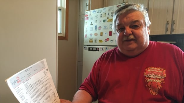 Reg Freund looks over one of the many bills he has recently received from Hydro One. One of the bills said he owed the utility $6300 for electricity at his seasonal summer property, north of Thunder Bay.