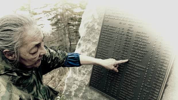 Eva Yassie points out Ila Oman's name on a memorial at the entrance of Dene Village near Churchill, Man.