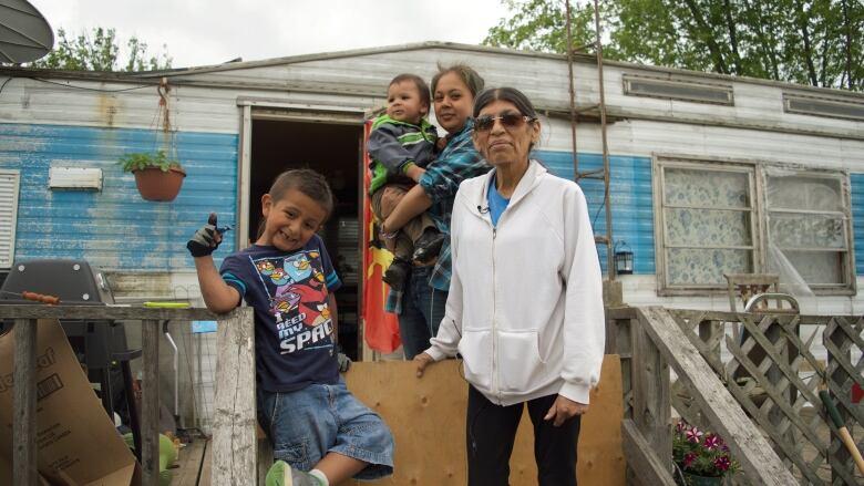 Flower Doxtador Stands With Her Grandchildren Outside Her