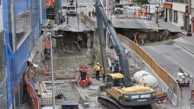 A worker surveys the Ottawa sinkhole Thursday morning as concrete is poured in to stabilize the area and protect the foundations of nearby buildings.