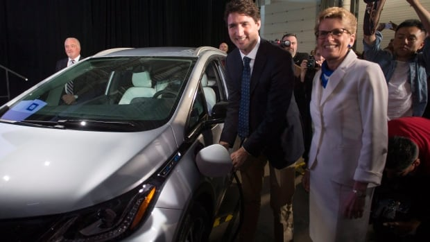 Prime Minister Justin Trudeau, left, and Ontario Premier Kathleen Wynne pose as they plug in a 2017 Chevrolet Bolt electric car at the announcement in Oshawa on Friday.
