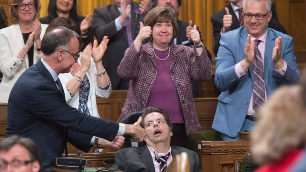 Members of Parliament applaud Ottawa-Vanier MP Mauril Bélanger, centre, as his private member's bill on changing a phrase in the Canadian anthem to make it gender-neutral is debated in the House Friday. It goes to a final Commons vote on Wednesday, when it is expected to pass — but the controversy may not end there.