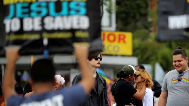 Women kiss as anti-gay protesters taunt people Sunday at the 46th annual Los Angeles Gay Pride Parade in West Hollywood, Calif. following the attack at a gay night club in Orlando, Florida.
