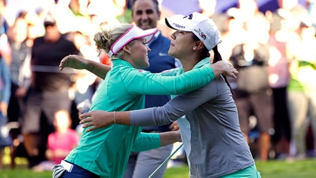 Brooke Henderson, of Canada, left, embraces Lydia Ko, of New Zealand, after Henderson won on the 18th green in a playoff hole in the Women's PGA Championship.
