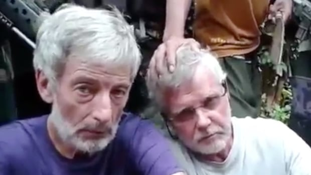 Canadians Robert Hall, left, seen in a video uploaded to YouTube, and John Ridsdel were executed in the Philippines by the militant group Abu Sayyaf earlier this year. The Canadian government has drawn criticism for how it handled their abduction.