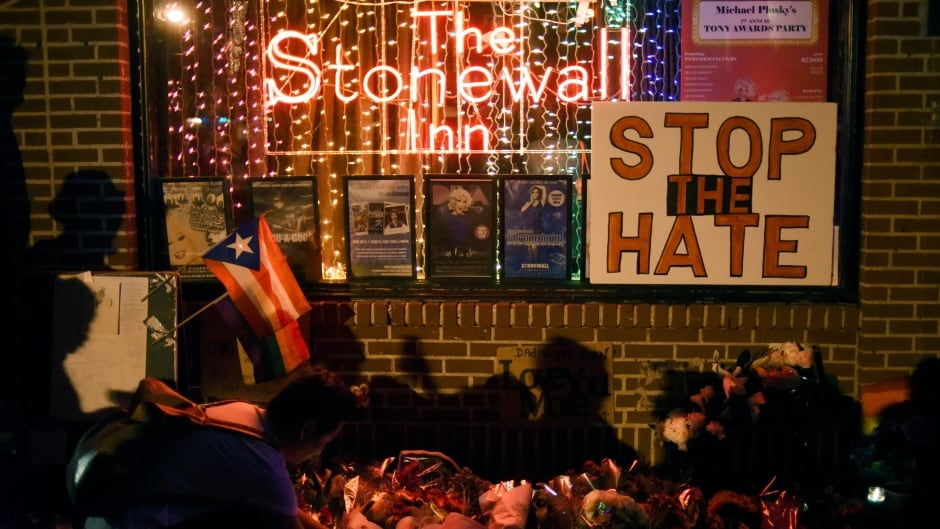 A man lights a candle at a memorial outside The Stonewall Inn following the shooting massacre at Orlando's Pulse nightclub on June 12, 2016.