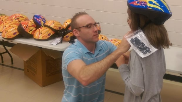 Duncan Macgillivray fits a bike helmet on a student at C.D. Howe school during the 2016 Bike Helmets for Kids campaign.