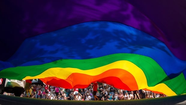 A large rainbow flag is carried down Robson Street during the Vancouver Pride Parade in Vancouver, B.C., on Sunday, August 2, 2015. For Ranier Oktovianus, an LGBT refugee from Indonesia, it was the first time he experienced a Pride event.